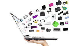 Online shopping concept. Modern laptop in the hand with lots of merchandise isolated on white Stock Image
