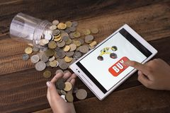 Online shopping concept. Boy buying toys online using digital tablet with coins and wooden background stock photography