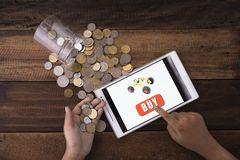 Online shopping concept. Boy buying toys online using digital tablet with coins and wooden background royalty free stock images