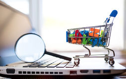 Online Shopping Concept. With Magnifying Glass And Miniature Cart royalty free stock image