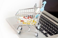 Online shopping concept pills. Online supplements pharmaceutical shopping concept, shopping-cart placed on laptop isolated Stock Image