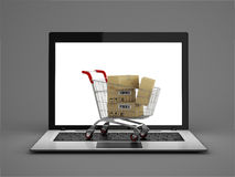 Online shopping concept. Shopping Cart with Boxes over Laptop Stock Images