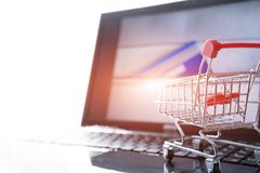 Online shopping concept. Shopping cart trolley on the laptop with a credit card on the zipper bag Royalty Free Stock Photos