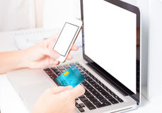 Online shopping concept. Someones hands holding mobile phone and credit card, making on-line payment, copy space on screen of laptop and phone screen Royalty Free Stock Photos