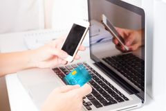 Online shopping concept. Someones hands holding mobile phone and credit card, making on-line payment Stock Image