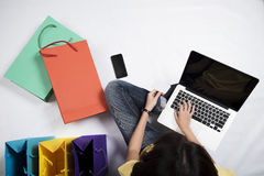 Online shopping concept. Top view of asian woman using laptop with black blank screen and colorful shopping bags, shoes on white floor. Online shopping concept Stock Photo