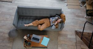 Online shopping concept. Young beautiful happy blonde woman relaxing on sofa using e-commerce smart phone app at home.