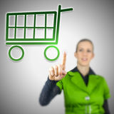 Online shopping concept. Young woman choosing shopping cart icon on virtual screen. Concept of online shopping Royalty Free Stock Photo