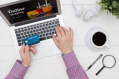 Online shopping with credit card. Man`s hands holding a credit card. Using laptop for online shopping, flat lay desk concept Stock Image