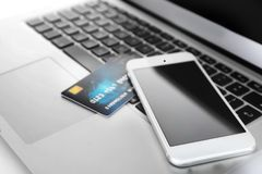 Online shopping. Credit card and smartphone on laptop`s Stock Image