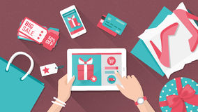 Online shopping. And delivery concept, woman buying fashion products from an e-shop using a digital touch screen tablet, flat lay Royalty Free Stock Images