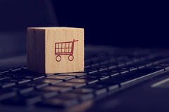Online shopping and e-commerce background. With a wooden cube showing a shopping cart icon resting on a computer keyboard viewed low angle over black with Stock Photo