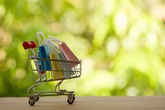 Online shopping, e-commerce concept: Paper shopping bags in a trolley or shopping cart  in the natural green background. purchase