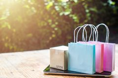 Online shopping, E-commerce, fast and easy trading concept : Col. Orful shopping bags, Paper carton on tablet depicts customers order things from retailer sites royalty free stock images