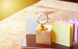 Online shopping, E-commerce,fast trading concept : Colorful shop. Ping bags, Paper carton with crystal globe and world map on tablet depicts customers order stock photos