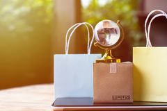 Online shopping, E-commerce,fast trading concept : Colorful shop. Ping bags, Paper carton with crystal globe and world map on tablet depicts customers order stock photo