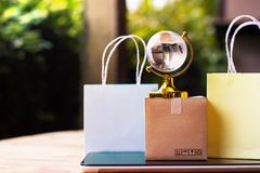 Online shopping, E-commerce,fast trading concept : Colorful shop. Ping bags, Paper carton with crystal globe and world map on tablet depicts customers order royalty free stock image