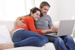 Online-shopping för lyckliga par som har gyckel på bärbara datorn på soffan Royaltyfri Foto