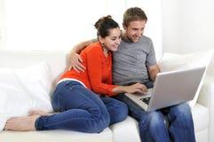 Online-shopping för lyckliga par som har gyckel på bärbara datorn på soffan Royaltyfri Bild
