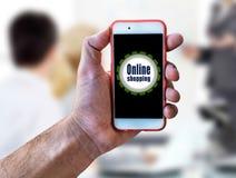 Online-shopping, hållande mobil för marknadsföringsbegreppshand Arkivfoto