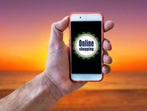 Online-shopping, hållande mobil för marknadsföringsbegreppshand på stranden Royaltyfri Fotografi