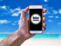 Online-shopping, hållande mobil för marknadsföringsbegreppshand på stranden Fotografering för Bildbyråer