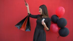 Online shopping, happy smiling girl makes purchases on Internet using mobile phone and plastic card in black Friday. Seasonal sale on background red wall stock video footage