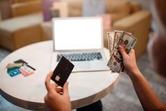 Online-shopping hemma Välja en betalningmetod mellan kreditering eller debiteringkort och kassa arkivbild