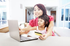 Online shopping at home. Young asian women online shopping using credit card with her daughter, shot at home Stock Images