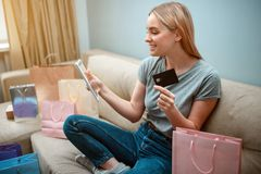 Online shopping at home. Young happy shopper with credit card and tablet is buying in online shop while sitting on a. Brown sofa with colorful shopping bags royalty free stock photo
