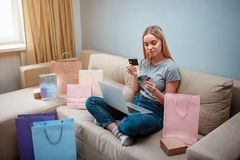 Online shopping at home. Young happy shopper with laptop is choosing best credit card for payment in online shop while. Sitting on a brown sofa with colorful royalty free stock photos