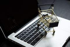 Online shopping bank card nearby a laptop and mini shopping cart. Online shopping. A laptop and mini shopping cart and gadgets Royalty Free Stock Images