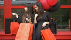 Online-shopping, lyckliga unga kvinnor med pappers- påsar i händer på röd bakgrund gör köpet den online-användande smartphonen lager videofilmer