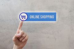 Online shopping - man hand pressing button. Online shopping - man hand pressing transparent blue virtual interface button with cart icon on grunge light brown stock photo