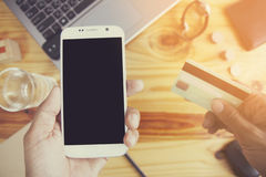 Online shopping. Man`s hands holding a credit card and using smart phone for online shopping Royalty Free Stock Photos