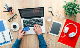 Online shopping. Man working at desk and purchasing products online, he is making a payment using a credit card, online shopping concept Stock Photo