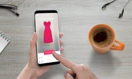 Online-shopping med den moderna mobiltelefonen Kvinnabruksklär online-lagret som köper rosa färger Royaltyfri Foto