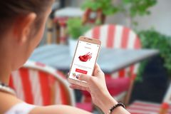 Online shopping with mobile phone. Red shoes on store web site. Woman use smart phone in coffee shop or restaurant Royalty Free Stock Image