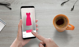 Online shopping with modern mobile phone. Woman use online store to buy pink dress. Modern smart phone with round edges. Coffee beside Royalty Free Stock Photo