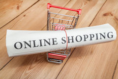 Online shopping newspaper and cart. On wooden floor royalty free stock photos