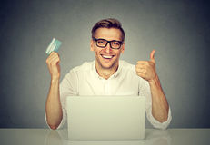 Online shopping payment. Man showing credit card using laptop Stock Images