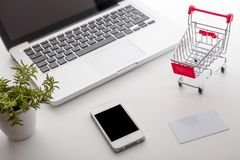Online shopping. Shopping cart, keyboard, bank card. Online shopping. Bank card nearby a laptop and mini shopping cart on white background top view Royalty Free Stock Photo