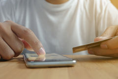 Online shopping with a smartphone device and a credit card. In the other hand Royalty Free Stock Images