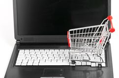 Online shopping. trolley on laptop. Isolated on white Stock Photo