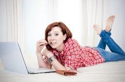 Online-shopping Worreid för röd haired kvinna på vit bakgrund Fotografering för Bildbyråer