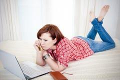 Online-shopping Worreid för röd haired kvinna på vit bakgrund Royaltyfri Bild