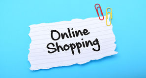 Online Shopping written on paper with blue background Royalty Free Stock Photography