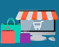 Online store. Computer with cart for shopping and bags Stock Photo