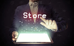 Online store  concept. Image of a man with a tablet in his hands. His hand touches the `store` button. Online store  concept Stock Images