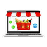 Online store concept on laptop screen with striped awning. Laptop with food basket on screen. Buy groceries online, food delivery, internet shopping concepts Stock Image